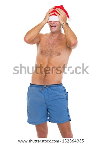 Smiling man in beach shorts pulling santa hat over eyes
