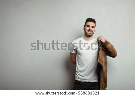 Smiling man in blank t-shirt and jacket, grey concrete wall background