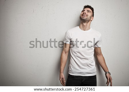 Smiling man in blank t-shirt, white grunge wall background - stock photo