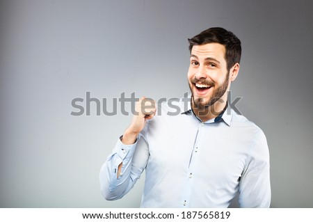 smiling man in blue shirt pointing back, on grey background - stock photo