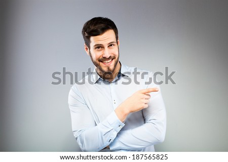 smiling man in blue shirt pointing, on grey background - stock photo