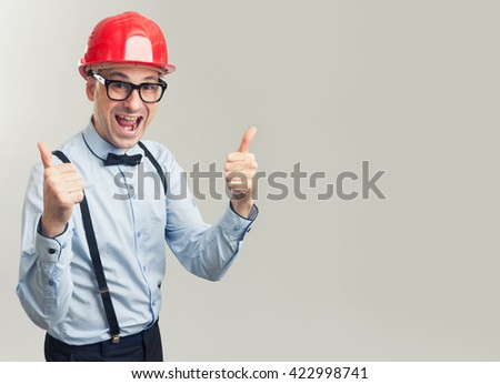 smiling man in construction helmet showing thumbs up - stock photo