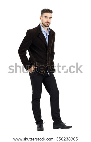 Smiling man in corduroy coat with hands in pocket looking at camera. Full body length portrait isolated over white studio background.