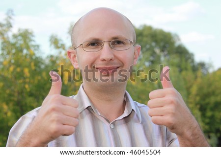 smiling man in early fall park with thumbs up gestures - stock photo