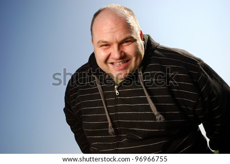 smiling man in front of blue sky - stock photo