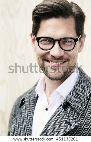 Smiling man in glasses and coat, portrait