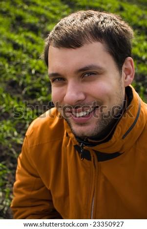Smiling man in orange jacket on blurry green grass - stock photo