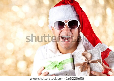 smiling man in santa helper hat with many gift boxes - stock photo