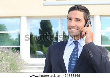 Smiling man in suit talking on cellphone - stock photo