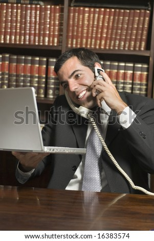 Smiling man in suit talks on two phones while holding laptop. Vertically framed photo. - stock photo