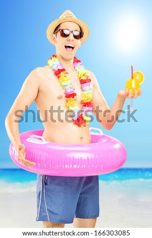 Smiling man in swimming shorts, holding an orange cocktail and posing on a beach next to a sea