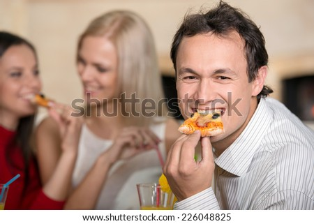 Smiling man is eating a pizza. Two girls are taking. - stock photo