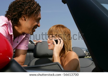 Smiling man leaning on a car near a young woman phoning - stock photo