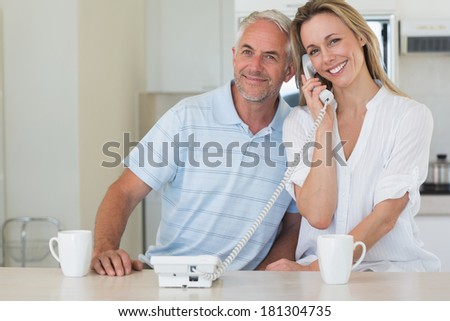 Smiling man listening in on his blonde partners phone call at home in the kitchen - stock photo
