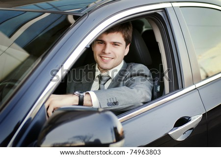 Smiling man looking from a car window - stock photo