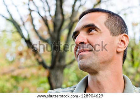 Smiling man looking up over the tree background - stock photo