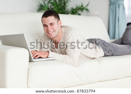 Smiling man lying on a sofa with a laptop while looking at the camera