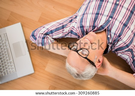 Smiling man lying on floor next to laptop in the living room