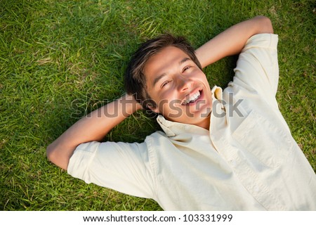 Smiling man lying with both hands resting behind his neck on the grass - stock photo