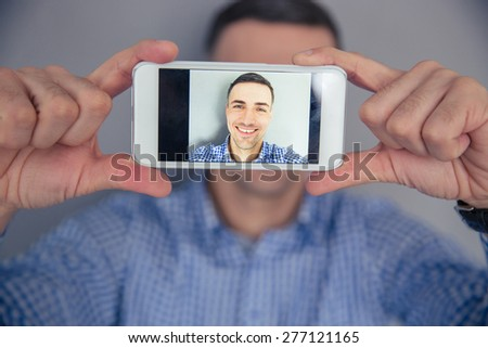 Smiling man making selfie photo on smartphone - stock photo