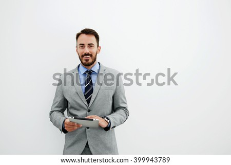 Smiling man managing director in luxury suit is holding portable digital tablet and looking at camera, while is standing in office against wall background with copy space for advertising text message - stock photo