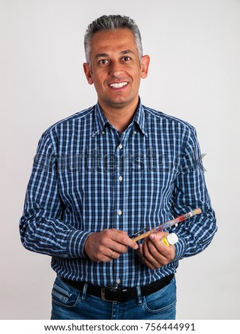 Smiling man of middle age with grey hair holding paintbrushes and paint dispenser, isolated on white background