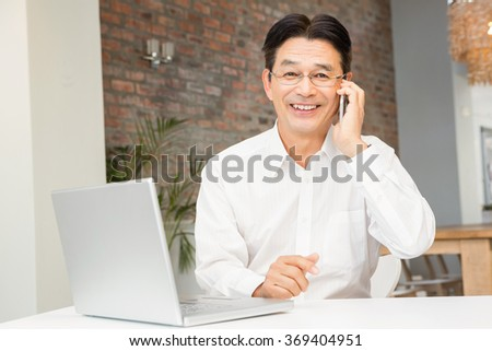 Smiling man on a phone call in living room
