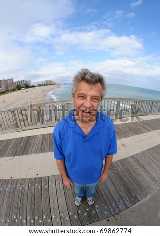 Smiling man on a pier - shot with a fish-eye lens - stock photo