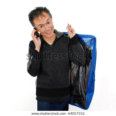 smiling man on cell phone carrying clothing  in  dry cleaning plastic bag. white studio background - stock photo