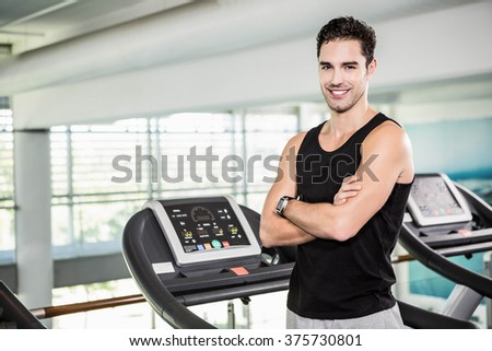 Smiling man on treadmill standing with arms crossed at the gym - stock photo