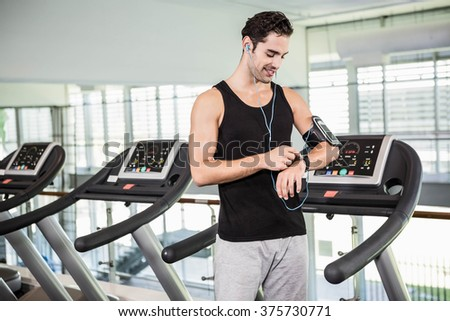 Smiling man on treadmill using smart watch at the gym - stock photo