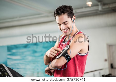 Smiling man on treadmill using smartphone in the gym - stock photo