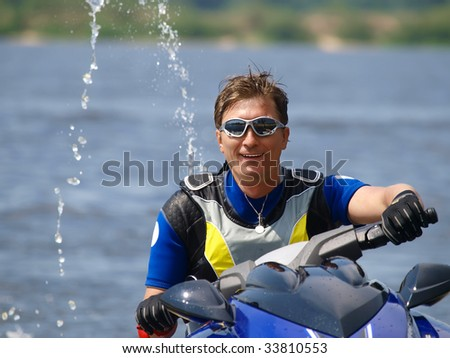 Smiling man on Wave Runner on summer river in daylight - stock photo