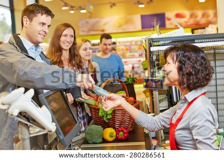 Smiling man paying groceries at supermarket checkout with Euro money bill - stock photo