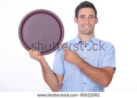 Smiling man pointing at an empty drinks tray - stock photo