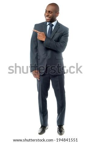 Smiling man pointing his finger towards something - stock photo