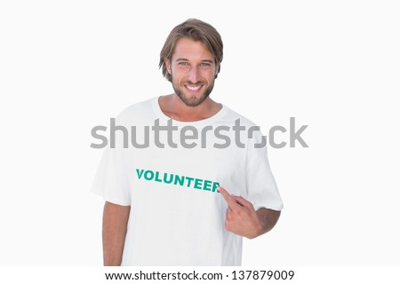 Smiling man pointing to his volunteer tshirt on white background - stock photo