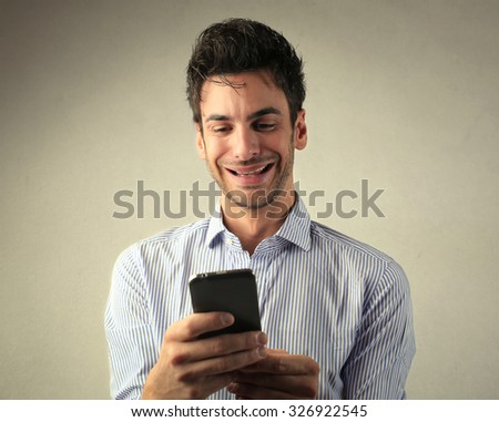Smiling man reading a text message - stock photo