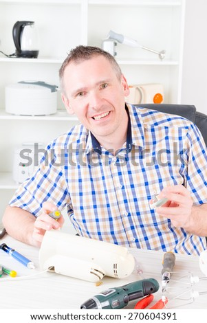 Smiling man repairing electric can opener at home appliance service workshop - stock photo
