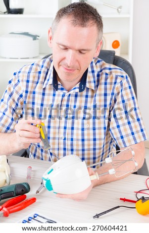 Smiling man repairing held food mixer at home appliance service workshop - stock photo