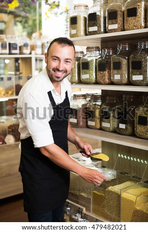 Smiling man seller wearing apron standing with cereals sold by weight in organic shop