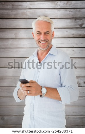 Smiling man sending a text message against wooden planks
