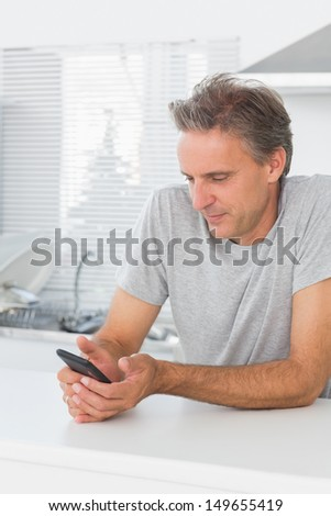 Smiling man sending text message in kitchen at home sitting at counter - stock photo