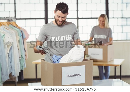 Smiling man separating clothes from donation box in office and woman seen in background