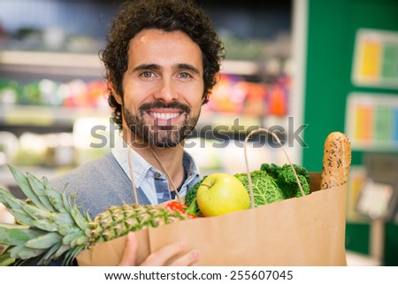 Smiling man shopping in a supermarket - stock photo