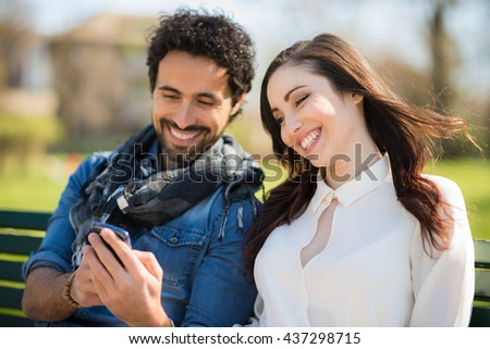 Smiling man showing his mobile phone to a girl. Shallow depth of field, focus on the woman