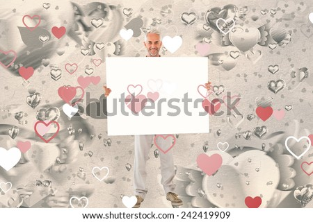 Smiling man showing large poster against grey valentines heart pattern - stock photo