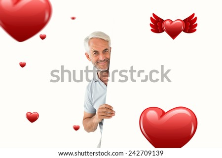 Smiling man showing large poster against hearts - stock photo