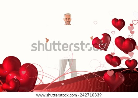 Smiling man showing large poster against valentines heart design - stock photo