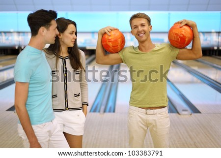 Smiling man shows arm muscles and holds two orange balls; pair look at him in bowling club; focus on right man; shallow depth of field - stock photo